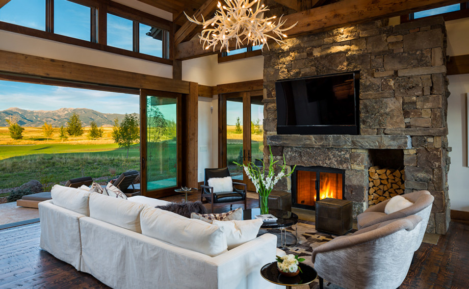 Great room with a stacked stone fireplace and beautiful views of the bridger mountains from a custom built home in black bull bozeman montana