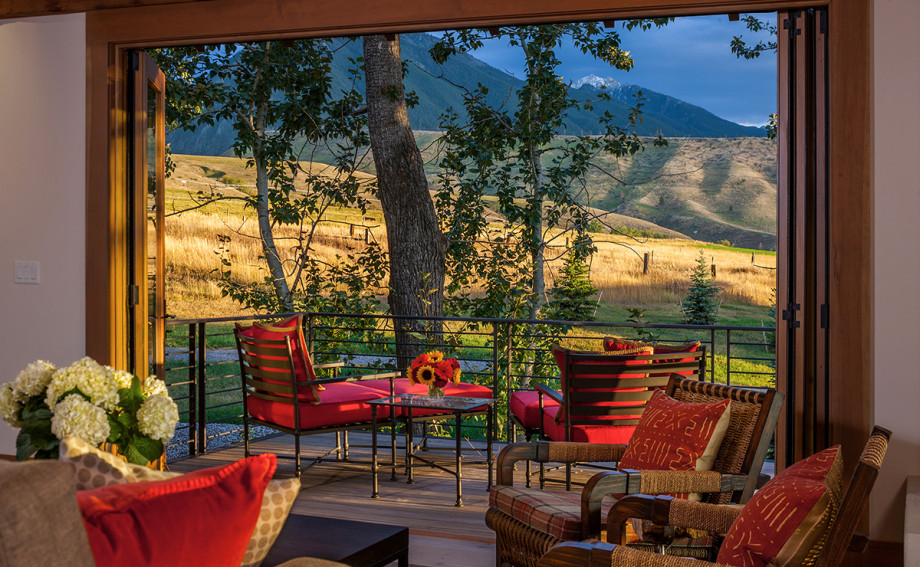 red chairs on the patio of an indoor-outdoor living rooom with views of the mountains in Paradise Valley