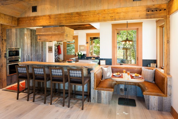dining is best done with friends and this kitchen has a cozy dining nook with custom barnwood siding and leather built-in seating