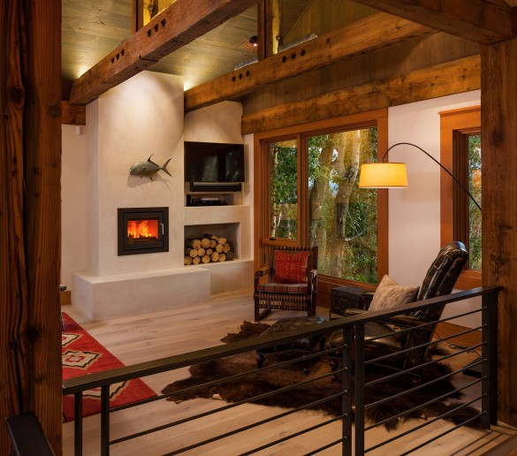 warm-hued exposed beams and a custom fireplace warm the interior