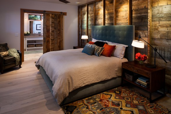a unique barnwood accent wall in contrast with a velvet headboard makes this bedroom one of a kind