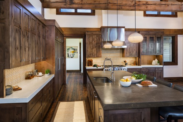 warm custom wood cabinets go perfectly with modern lighting in this amazing custom montana kitchen